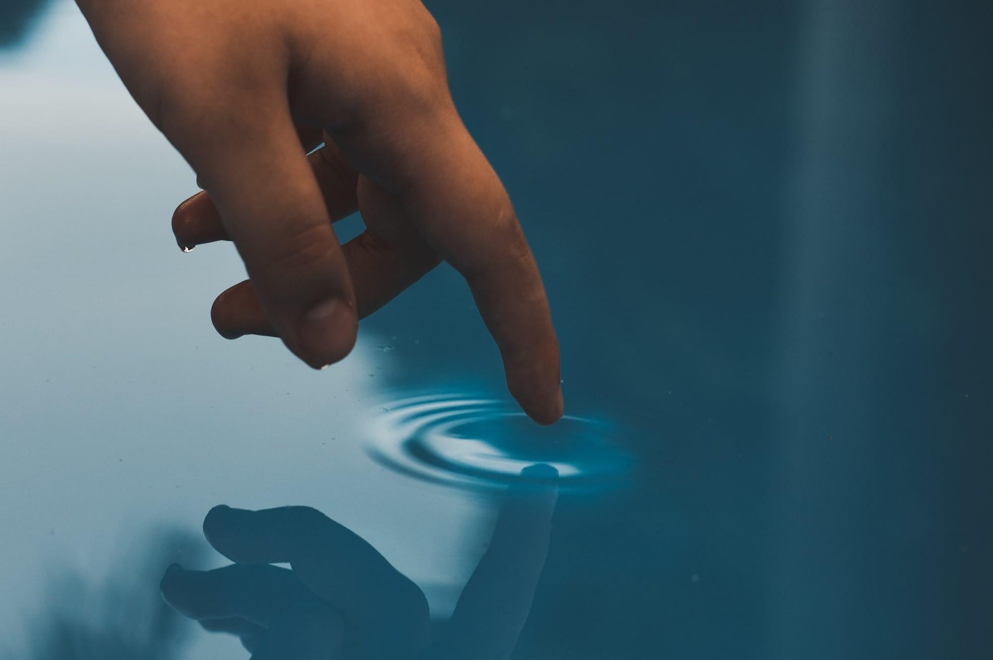 finger touching pool water